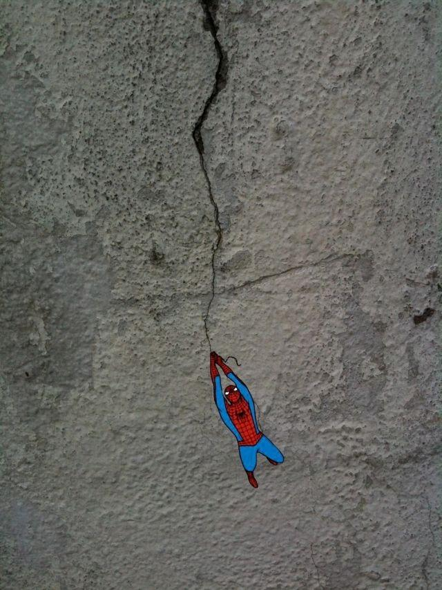 Urban Interventionists Depict Spiderman Swinging from a Crack in the Wall