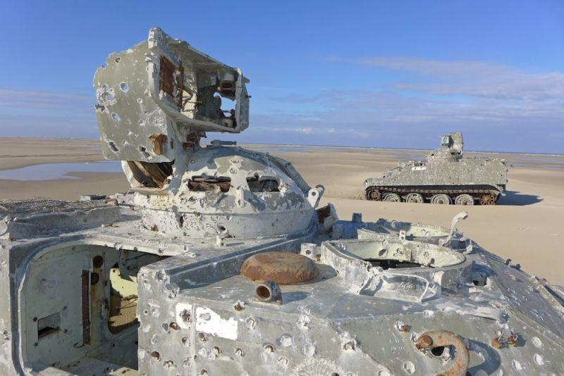 Derelict carcasses of abandoned infantry fighting vehicles litter the beach